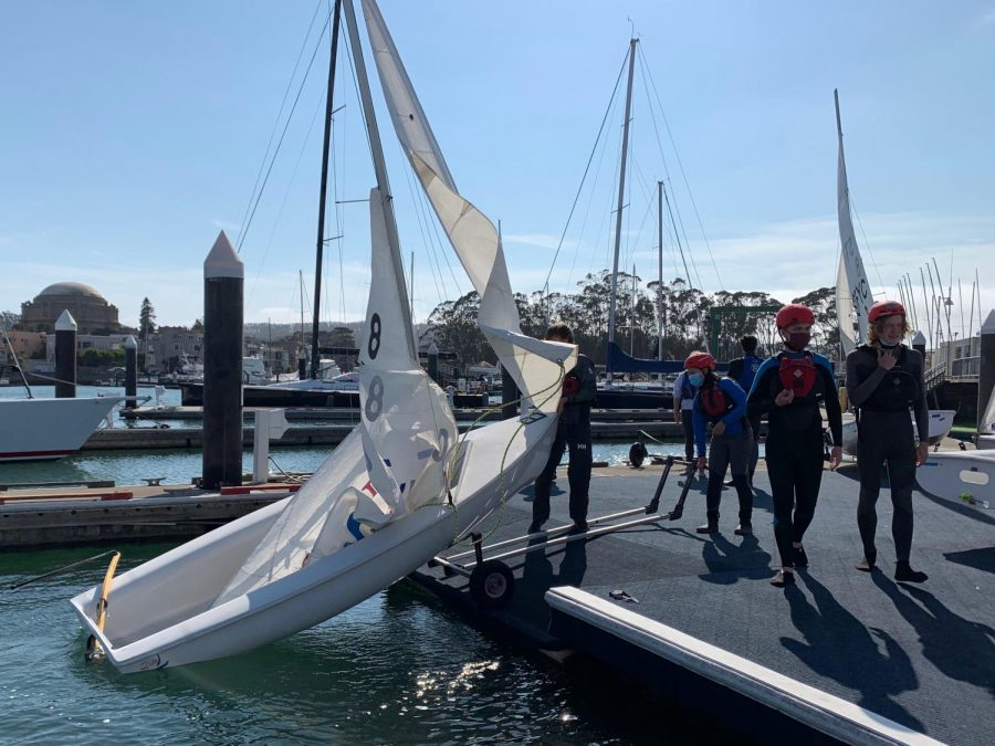 Sophomore Natalie Tonkovich and senior Sebastian Green launch Boat 8 at the St. Francis Yacht Club on Sept. 8. Sailors returned to practice twice a week this fall season.